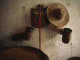 A Straw Hat  Straw Baskets and a Belt Hang on a White Wall