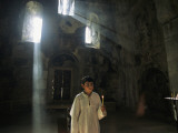 An Altar Boy Holds a Candle Inside a Dimly-Lit Church