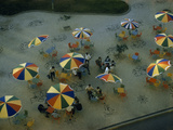 Mosaics and Rainbow-Colored Cafe Umbrellas Decorate a City Sidewalk