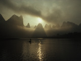 A Man in a Small Boat in Morning Mist Shrouding Karst Hills