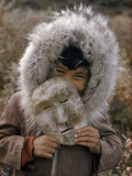 A Nunamiut Boy in a Fur-Trimmed Parka Holds a Mask of Caribou Hide