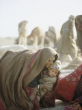Wrapped Against Wind and Sand  a Kuchi Woman Lifts a Young Child