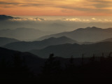Sunset Casts a Colorful Glow over Mountaintops Shrouded in Fog
