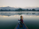 A Woman in a Rowboat Gazes at the Annapurna Range at Dawn