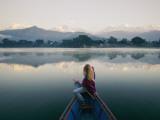 A Woman in a Rowboat Gazes at the Annapurna Range at Dawn