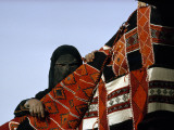 A Veiled Bedouin Woman Peers Through a Slit-Eyed Veil