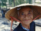 An Elderly Vietnamese Woman in a Native Hat Smiles as She Is Photographed