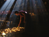 A Buddhist Monk Lights Devotional Lamps Inside Jokhang Temple