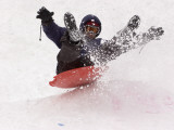 A Man Sleds Down a Hill During a Snowstorm