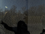 Shadow of a Woman Pointing to a Name on the The Vietnam Memorial