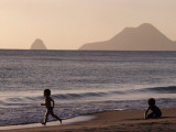 A Child Running and Another Playing on a Beach Along the Shoreline