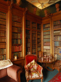 A Red Chair Sits Amid Shelves of Books in Balfour Castle's Library