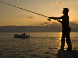 A Man Fishing from the Shore and a Fishing Boat in Water at Sunset