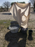 A Woman Washes Laundry by Hand and Dries it in the Sun