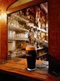 A Pint of Dark Beer Sits in a Pub Service Window Papier Photo par Jim Richardson