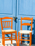 Orange Chairs Cast Shadows on Blue Padlocked Doors