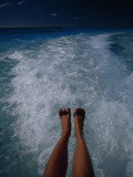A Woman's Feet Dangle over the Churning Wake of a Motorboat