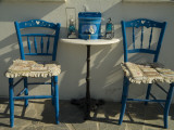 A Pair of Blue Chairs and a Table with Lamps and a White Stucco Wall