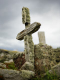 An Old Moss-Covered Cross Stands Amid Rocks in a Graveyard