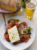 A Greek Salad  a Basket of Bread and Greek Beer