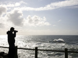 A Silhouetted Photographer Takes a Pictures of the Rugged Coastline at Sunet