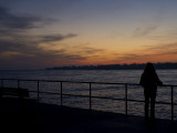 A Silhouetted Woman on a Pier Looks across to a Lighthouse at Sunset