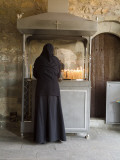 A Nun Lights Candles at a Shrine at One of the Monasteries in Meteora