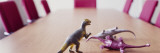 Three Dinosaur Toys on a Conference Table