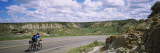 Man Cycling on a Road  Badlands  Theodore Roosevelt National Park  North Dakota  USA