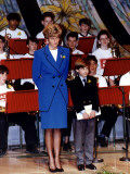 Princess Diana dressed in blue with Prince William standing in front of a Welsh orchestra