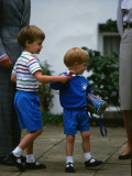 Prince Harry wearing a blue sweatshirt shorts and thomas the tank engine bag with Prince William on