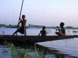 Three Boys Play on a Canoe (Pirogue) on the River in Mopti