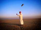 Arab Handler Swinging Lure During Hunting Falcon Training Exercise in Desert