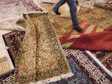 Salesman Walks on Carpets for Sale at Carpet Factory