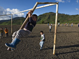 Boy Climbing Goal Post  with Corn Fields on Slopes of Acatenango Volcano in Background