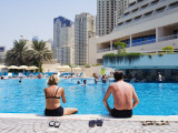 Couple Sitting by a Swimming Pool in the 40 Degree Heat