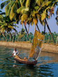 Man Paddling Small Canoe with Sail Near Ayiramthengu