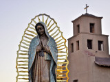 Mother Mary Sculpture with Church Belltower in Background