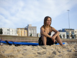 Woman Sitting on Beach with Surfboard at Bondi Beach