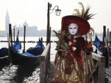 Masked Person in Costume by Gondolas Near St Mark's Square