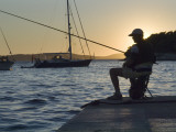 Man Fishing at Sunset at Port