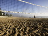 Person Jogging Near Volleyball Net on Manly Beach  Early Morning