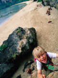 Young Boy Climbing Rocks Above Beach
