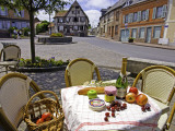 Cheese  Cherries  Apples and Champagne on Cafe Table with Half-Timbered House in Background