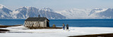 Two Hikers Standing On The Beach Near a Hunting Cabin  Bellsund  Spitsbergen  Svalbard Islands