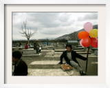 An Afghan Boy Sits on a Grave Plot and Sells Balloons and Eggs as Others Relax