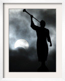 A Statue is Seen against a Cloudy Sky and a Partial Solar Eclipse