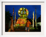 Children Walk Past an Illuminated Statue of Lord Buddha