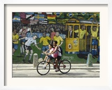 Two Children Ride Their Bicycle Pass a Mural
