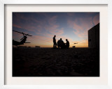 A UH-60 Black Hawk Crew Carry Out a Mission Brief at Sunset